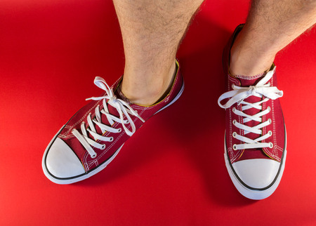 unworn: White male human legs and feet wearing a pair of red canvas trainers with background Stock Photo