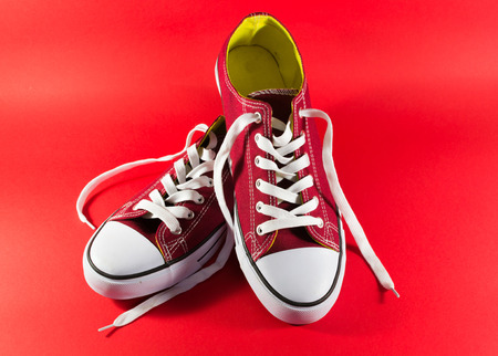 unworn: Simple burgandy and white colored trainers on a red background