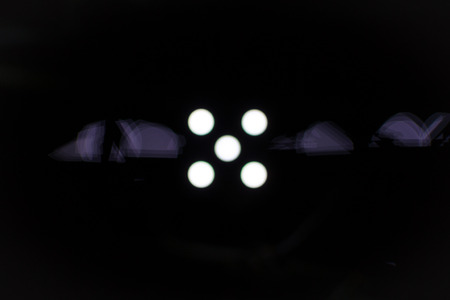 horizontal position: Five white dots on a black background with light defraction in a horizontal position