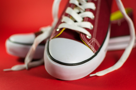 unworn: Red canvas trainer rubber sole detail on a cherry red background Stock Photo