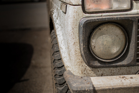 Muddy white jeep covered in dried mud and headlamp with copyspace photo