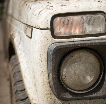 Muddy white jip covered in dried mud and headlamp photo