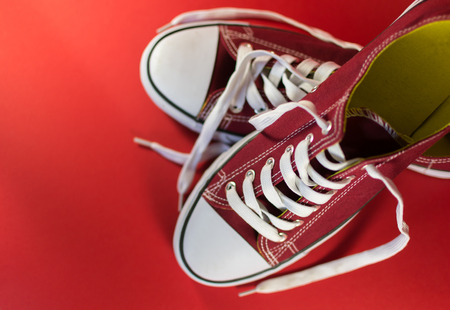 unworn: White and red canvas trainers on a crimson background