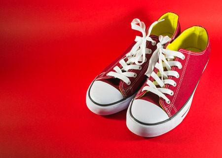 unworn: Pair of new red canvas trainers on a dark-red background