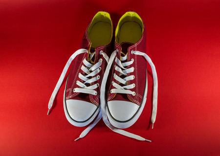 unworn: Single pair of cherry colored canvas trainers on a dark crimson background Stock Photo