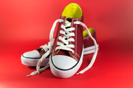 unworn: Pair of red canvas trainers on a maroon background