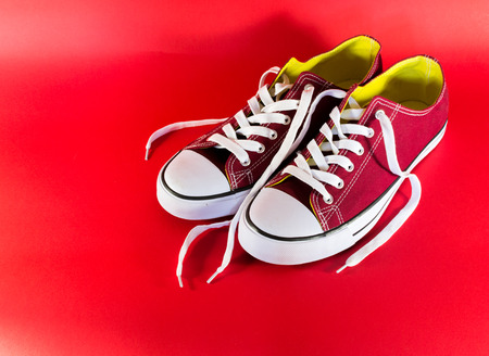 unworn: Red and white canvas style sneakers on a red backround