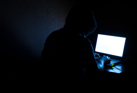 crime: Single solitary computer hacker works in the dark committing crime