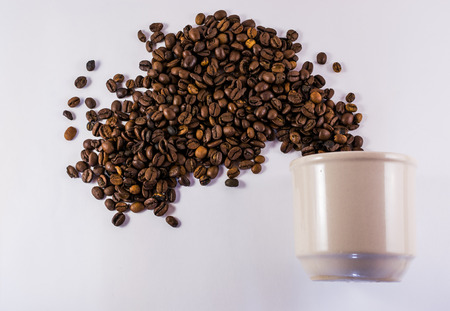 outwards: White single cup of coffee and exploding beans spreading outwards Stock Photo