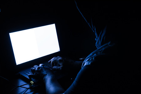 computer virus protection: Single solitary computer hacker works in the dark committing crime