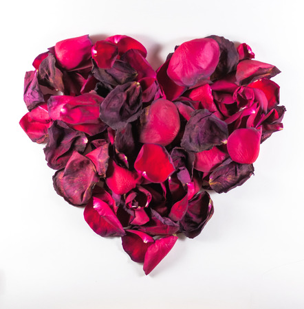 Decaying rose petals formed into a heart shape on a white background