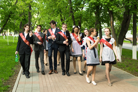 Group of Russian schoolchildren in traditional uniform celebrating graduation from high school in May 2015