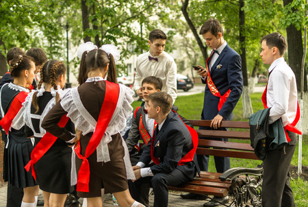 graduation suit: Group of Russian schoolchildren in traditional uniform celebrating graduation from high school in May 2015
