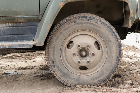 travelled: Single vehicle wheel in closeup covered in dust and dirt