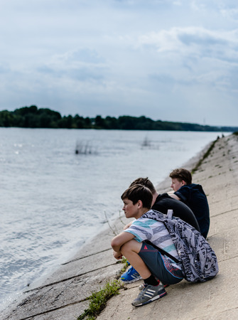 Three school children in casual clothing relaxing by the river in Ufa May 2015