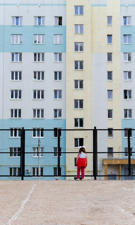 dismal: Single girl looking through a fence at apartment block