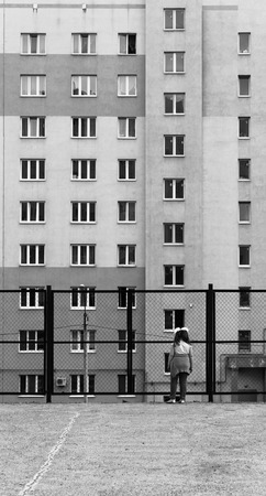 alienated: Single girl looking through a fence at apartment block in black and white Stock Photo
