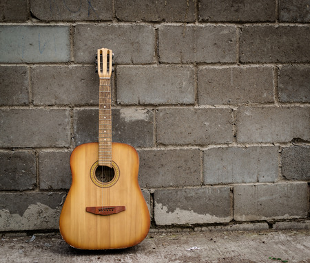 trashed: Single antique guitar resting against a grey brick wall