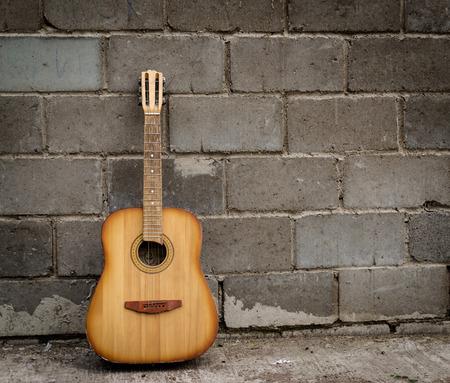 guitarra: Solo de guitarra antigua de descanso contra una pared de ladrillo gris
