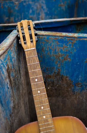 unwanted: Old unwanted guitar thrown away in an rusty metal dumpster