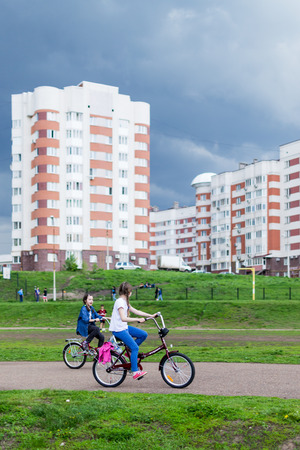 hurrying: Two children riding bikes as a spring storm and dark clouds approach in Ufa Russia in May