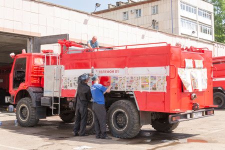 redecorating: Firemen in Ufa Russian redecorating a fire vehicle in the summer heat of May 2015 Editorial