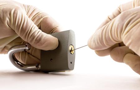 ladron: Abrir un candado de metal gris cerrada con un pico Ladrón Foto de archivo