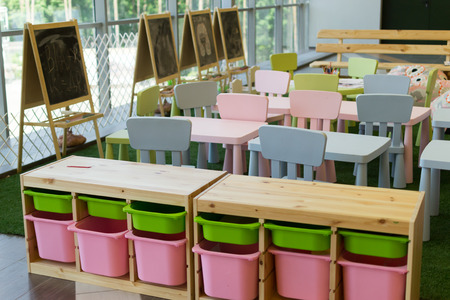 Modern empty kindergarten chairs and desks with chalkboards