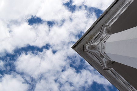 roman column: White marble style Greek Roman column against a blue sky and clouds Stock Photo