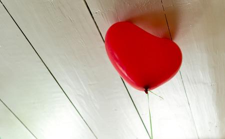 gravedad: Helio solitario globo lleno tratando de escapar de la gravedad contra un techo de madera blanca