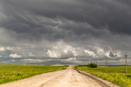 Solitary dirt track leads to the horizon as dark rain clouds gather overhead Stok Fotoğraf