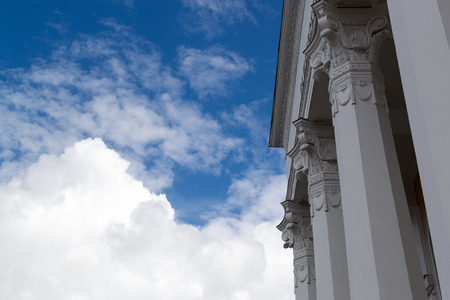 roman columns: White marble style Greek Roman columns against a blue sky and clouds Stock Photo