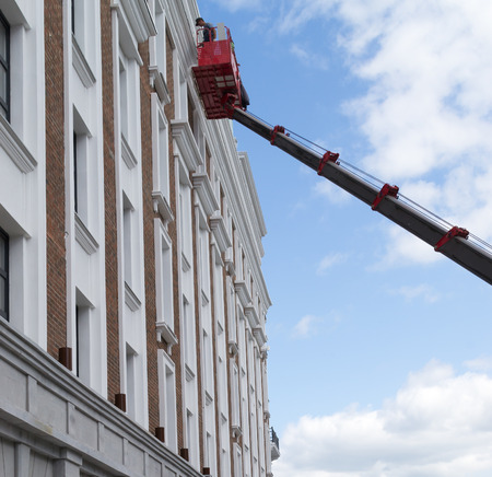 hydraulic lift: Workers working on a building facade using a red hydraulic lift Stock Photo