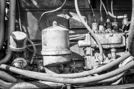 engine compartment: Close-up of a oil stained engine compartment of a yellow industrial earth excavator machine in monochrome Stock Photo
