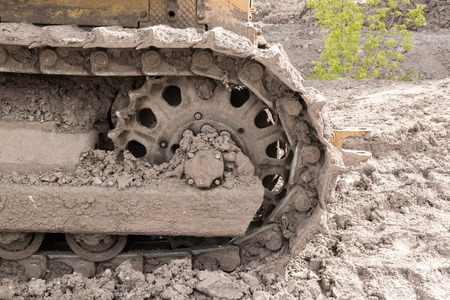 earth moving: Mudstained Caterpillar tracks of a yellow earth moving digger at rest Stock Photo