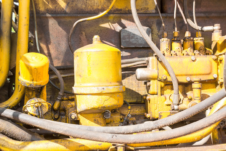 engine compartment: Close-up of an oill stained engine compartment of a yellow industrial earth excavator machine in monochrome Stock Photo