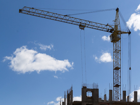 maneuverable: Single yellow metal construction crane against a blue white cloudy sky working on a new office building Stock Photo