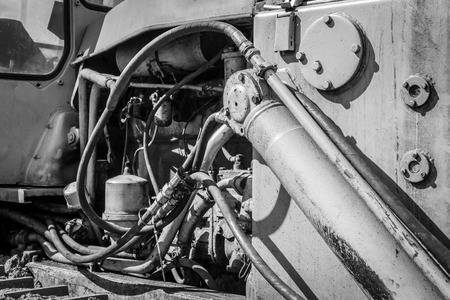 engine compartment: Close-up of a engine compartment of a yellow industrial earth excavator machine in monochrome