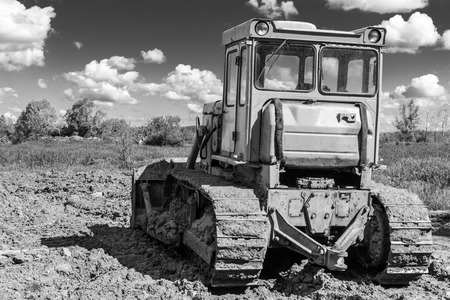 earth moving: Single earth moving digger covered in mud in black and white with cloudy sky