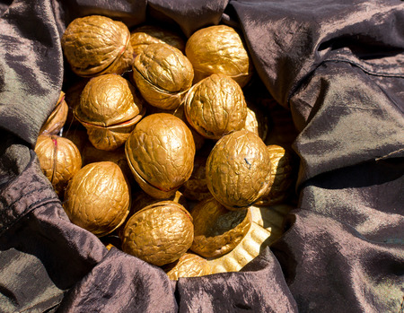 black satin: Pile of golden painted walnuts resting on black satin in natural sunlight Stock Photo