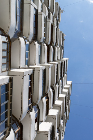 bleakness: Looking up at modern apartments forming a symmetrical architectural abstract pattern
