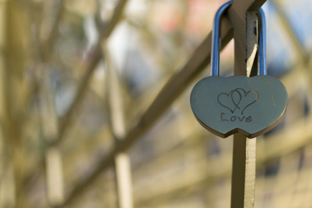 lock symbol: Single golden love padlock with two linked hearts