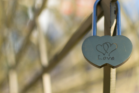 unbreakable: Single golden love padlock with two linked hearts