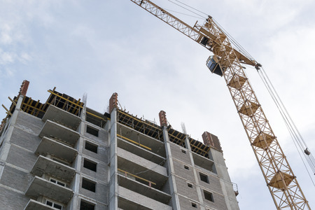 buildingsite: Yellow construction crane towers above newly built housing apartments