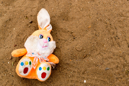 sand pit: Muticolred rabbit toy left in an empty sand pit