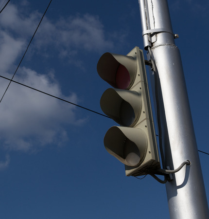 unlit: Unlit traffic signal on a silver post against a blue cloudy sky Stock Photo