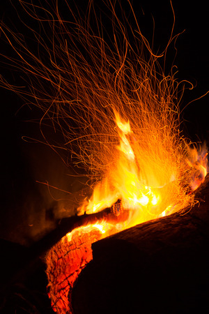 Sparks from a log burning campfire at night