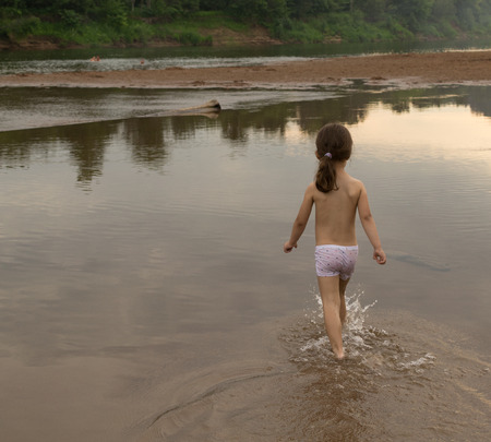 wade: Young girl wades through river waters at sunset Stock Photo