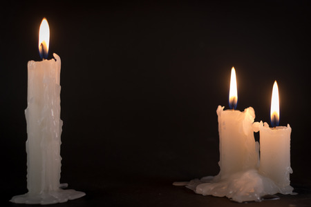 burning time: Three white candles burning during the darkness of night time
