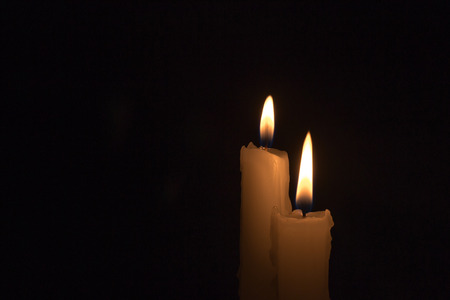 burning time: Two white candles burning during the darkness of night time Stock Photo